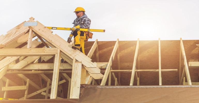 Roofing Contractor with Spirit Level in His Hand on Top of Newly Built Wooden House Roof Structure