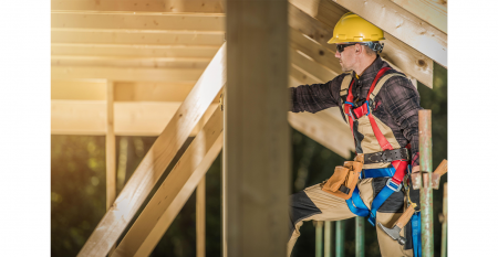 Construction Contractor Wearing Safety Harness and Hard Hat. Wooden House Skeleton Frame Building. Industrial Theme.