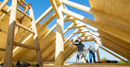 Builders at work with wooden roof construction